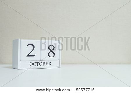 Closeup white wooden calendar with black 28 october word on blurred white wood desk and cream color wallpaper in room textured background with copy space selective focus at the calendar