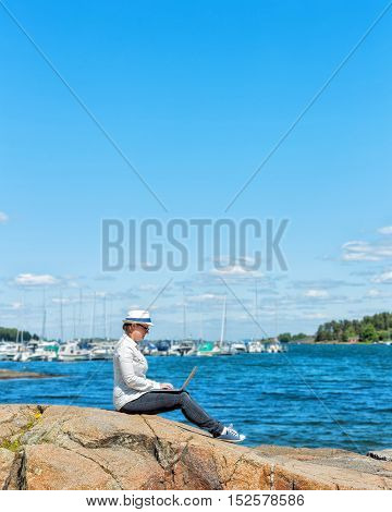 Profile of a self employed woman working with a laptop on the beach with the sea in the background