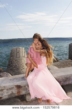 Portrait of a mother with her daughter,backdrop of the sunset over the sea