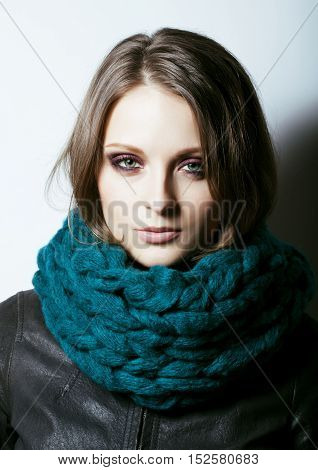 young pretty real woman in blue sweater and scarf all over her face smiling