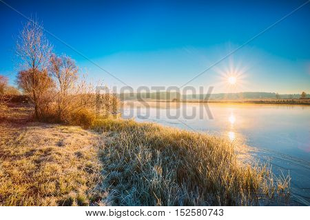 Sun Rises Over River. Autumn Frost Frozen River Covered With Thin Ice. Grass Covered With Frost. Sunrise, Sunset Over Autumn River