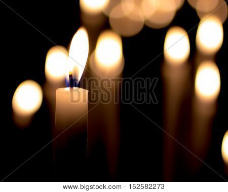 closeup of a burning candle on a dark background with soft lighting