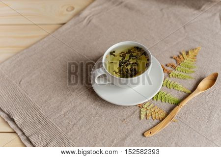 cup of tea with fern on a wooden light background