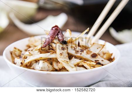 Stir fried cabbage in wok with Sichuan pepper, dried chili and soy sauce in white bowl, decorated with whole pods of chili peppers. Chopsticks and frying pan wok next to it, on wooden table