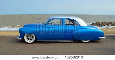 FELIXSTOWE, SUFFOLK, ENGLAND - AUGUST 27, 2016: Customized blue vintage car on seafront promenade, sea and beach in background. .