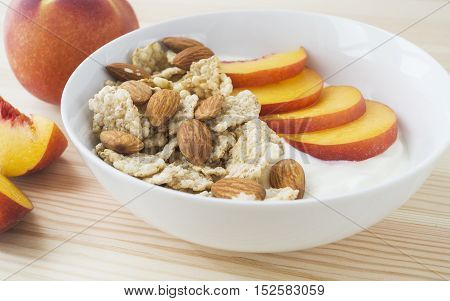 Whole grain cereal with fresh peach fruit yogurt and almond in white bowl. Healthy breakfast. Health and diet concept selective focus horizontal
