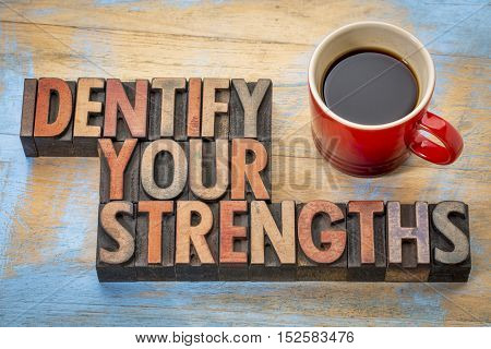 Identify your strengths - word abstract in vintage letterpress wood type blocks stained by color inks with a cup of coffee