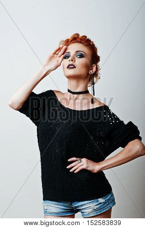 Studio Portrait Of Red Haired Girl On Black Blouse And Jeans Shorts With Bright Dark Make Up
