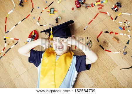 little cute preschooler boy among toys lego at home in graduate hat smiling posing emotional, lifestyle people concept close up