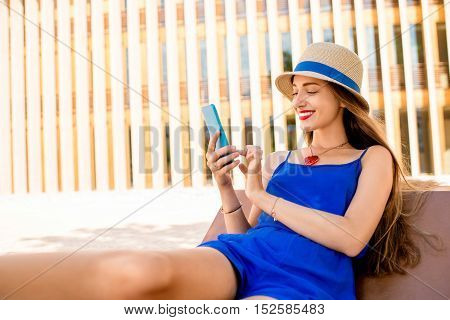 Young woman in blue dress talking with phone outdoors on the modern wall background