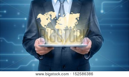 Businessman holding a tablet pc computer with the projection screen of graphic world map. Business concept. Digital presentation. International communication.