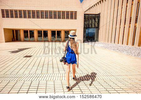 Vaduz, Liechtenstein - July 01, 2016: Young female tourist walks near the Parliament building in Vaduz, Liechtenstein