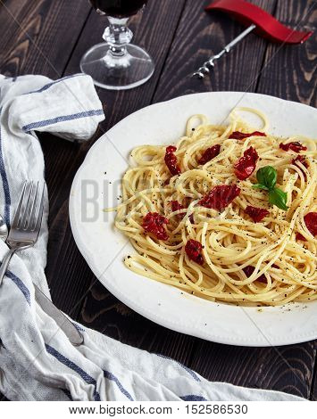 Vegetarian Italian pasta, spaghetti with sun-dried tomatoes on white plate, decorated with sprig of fresh Basil and sprinkled with ground black pepper. Cooked al'dente. Glass of red wine behind