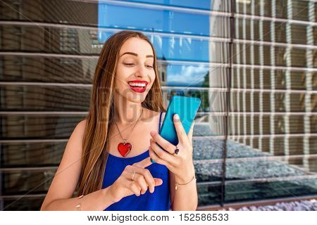 Beautiful woman using phone outdoors on the modern window background