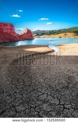 Oasis. Soil in dry season and lake with water.