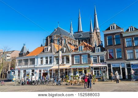 Delft, Netherlands - April 8, 2016: Colorful street view with traditional dutch houses on the square, church domes, bicycles, people walking in downtown of popular Holland destination