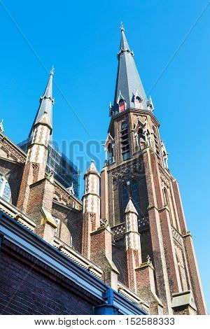 Colorful view of church tower in in downtown of popular Holland destination Delft
