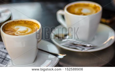Two cups of coffee on a table with ashtray in blured background