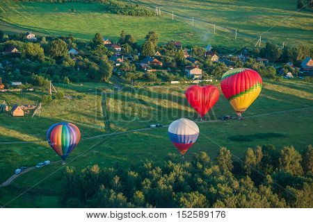 YAKHROMA RUSSIA - JUNE 23 2015: Colorful hot-air balloons are flying over the countryside.
