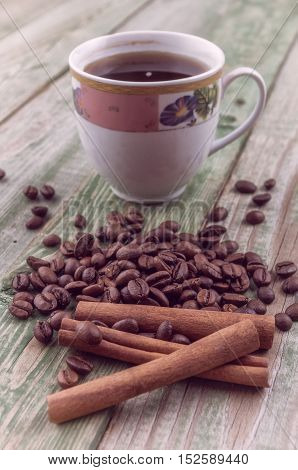 Cinnamon sticks on coffee beans with coffee cup on old rustic background. Wood texture