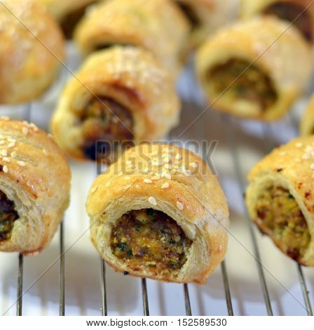 Sausage Rolls: Small bite-sized appetizers cooling on a wire rack.