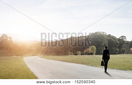Elegant businesswoman on road standing with back and looking ahead