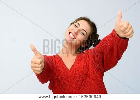 Happy young woman showing thumbs up on grey background