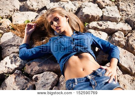 Caucasian long hair model in jeans shirt on rocks.