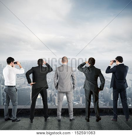 Businessmen looks at the city from the roof with binoculars