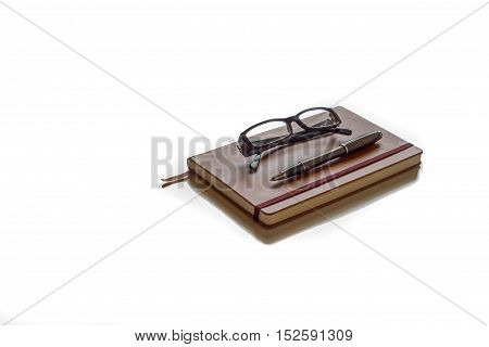 Glasses and pen ready to write on top of brown agenda with white background
