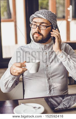 Arab man is drinking coffee in a cafe. He sits at a table in a restaurant on the tablet and drink coffee in soft sunlight from the window.