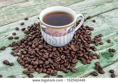 Cup coffee with beans on green wood table. Rustic wood texture.