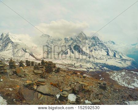 On top of mountain in Himalaya Nepal. Huge ice peaks of Everest. Snow landscape with rocks and stone pyramids. Trekking in Sagarmatha. Trekker and mountaineer memorable marks. Sport in severe climate
