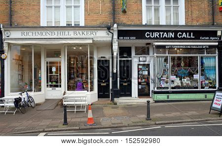 London, England - February 04, 2016: A Bakery with people in the window next to a Curtain store on Richmond Hill, London. The borough of Richmond is in the top five for highest average property values