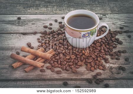 Hashtag as cinnamon sticks on coffee grains with coffee cup on old rustic background. Vintage