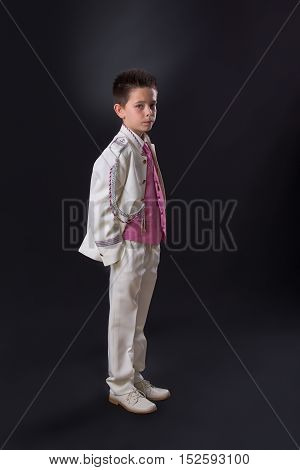 Young Boy Standing Seriously In His First Holy Communion