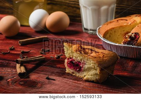 Piece of cherry cake with some ingredients on redwood table