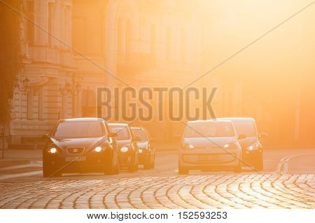 Vilnius, Lithuania  - July 8, 2016: Black Seat Leon And White Volkswagen Eco Up Cars Are At The Head Of Traffic On Zygimantu Street, The Paved Road In Yellow Sunlight Of Sunset Or Sunrise. Copyspace