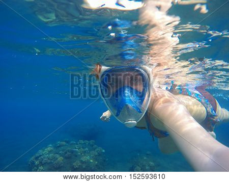 Woman underwater in full face snorkeling mask. Modern swimming gear. Selfie during dive in open water. Seaside sport activity on summer vacation. Coral reef landscape with blue depth image