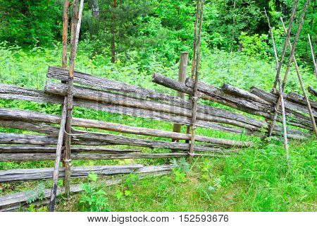 Traditional Finnish rural wooden fence. Forest in the background.