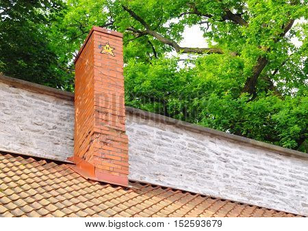Red brick chimney with a painted yellow star
