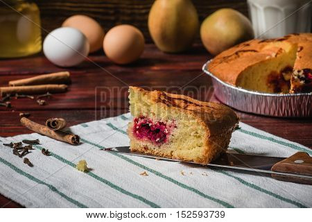 Slice of cherry cake on a striped towel and other objects on background.
