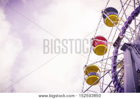 Vintage ferris wheel on the blue sky with clouds