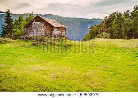 Old abandoned wooden house on a background of the Norwegian mountains. Summer nature Norway.
