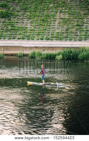Vilnius, Lithuania - July 08, 2016: Young Man Practice Stand Up Paddling SUP Or Standup Paddle Boarding On Neris River