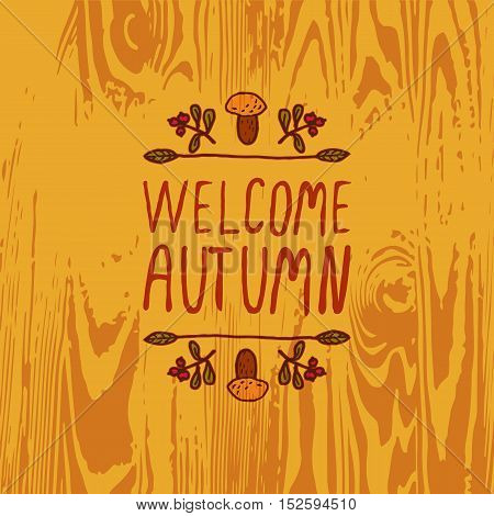 Hand-sketched typographic element with mushroom, berries and text on wooden background. Welcome autumn