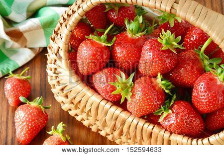 close up from strawberries in basket on the wooden table.
