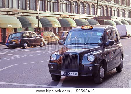 LONDON UK - February 09: Traditional taxi service black cab car on street with other cars in background near Harrods department store in London UK - February 09 2015; Public street on Knightsbridge with black cab waiting for the traffic light to turn gree