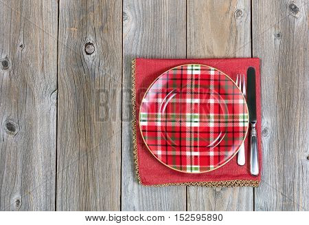 Overhead view of a festive Christmas dinner setting and cloth place mat on top of rustic wood