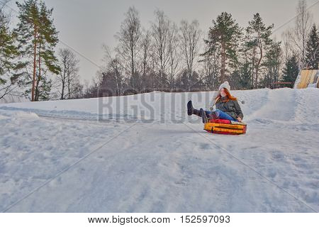 Happy teenage girl enjoying a winter sleigh ride on a slope